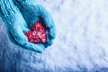 Woman hands in light teal knitted mittens are holding beautiful entwined vintage red heart in a snow. St. Valentine concept.