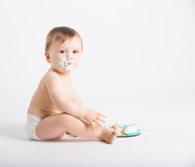 a cute 1 year old sits in a white studio setting. The boy looks to his left with a face full of cake frosting with half eaten cake. He is only dressed in a white diaper
