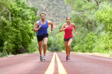 Determined man and woman running on road against trees. Runners sprinting in Full length of sporty male and female are in sports clothing. Athletic runner fitness sport couple are exercising outside.