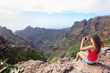 Woman photographing mountains while sitting on cliff. Young female is using smart phone to click picture of beautiful nature. Rear view tourist visiting Tenerife, Masca Valley, Canary Islands, Spain.