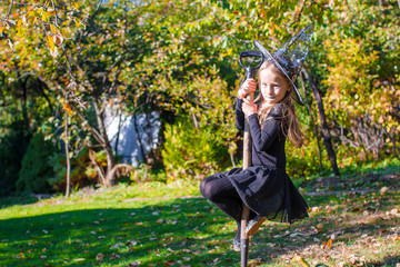 Wall Mural - Adorable little girl in halloween witch costume having fun on broom