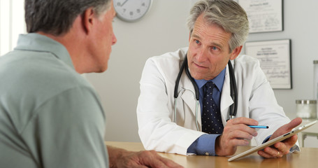 Mature doctor talking with patient and tablet in office