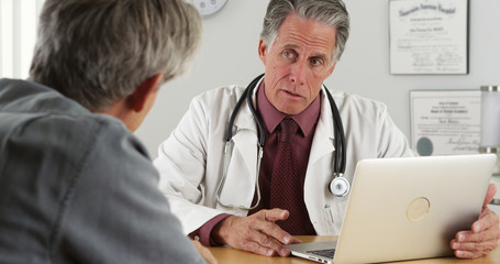 Doctor and senior patient talking at desk