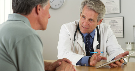 Senior doctor talking with patient and tablet in office