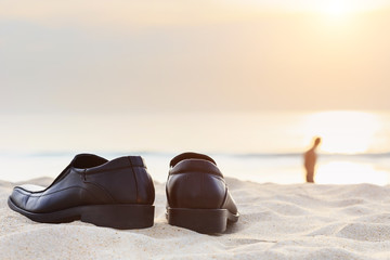 Black man leather shoe on the beach