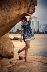 brunette girl in short frock high-heel shoes stands under rock