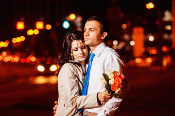 Elegant dressed man is tenderly embracing beautiful woman