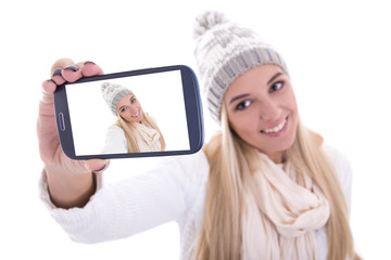 beautiful blond woman in winter clothes taking selfie photo with