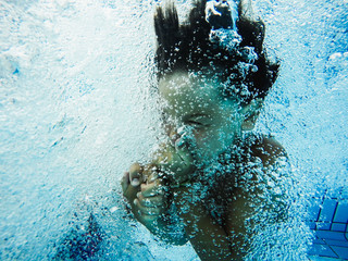 Boy holding his nose, jumping into a swimming pool