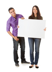 Young Smiling Couple Hold Up Blank Sign