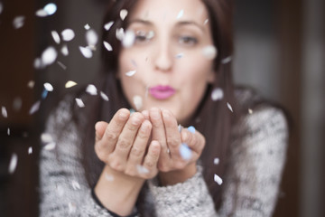 Woman blowing confetti in her hands