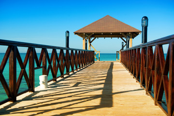 Wooden pontoon with canopy and with fence stretching into the sea