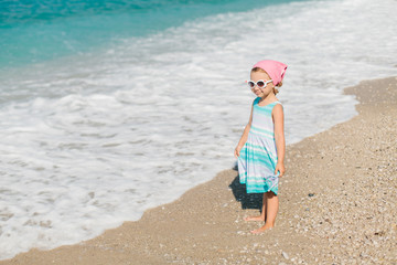Adorable happy smiling little girl with curly hair on beach vaca