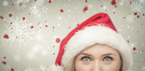 Composite image of festive blonde looking up in santa hat