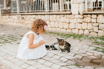 Little girl playing with cat outdoor
