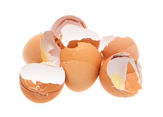 Broken brown eggs on a white background