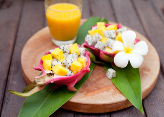 Tropical fruit salad in pitahaya, dragon bowls with mango juice.
