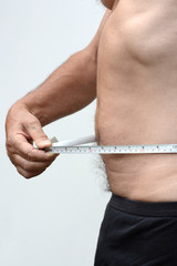 Male stomach in profile with tape measure
