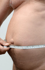 Fat male stomach with tape measure