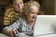 Elderly woman working on laptop with the help of his granddaughter.