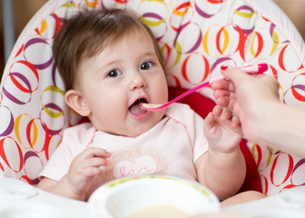 baby kid girl eating food with mother help