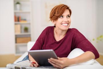 lachende junge frau sitzt auf dem sofa und hält tablet in der hand