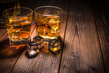 Two glasses of whiskey with ice on wooden table