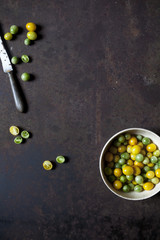 Overhead shot of yellow and green tomatoes on bowl on a rusty table