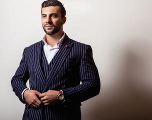 Elegant young handsome man in classic dark blue costume. Studio fashion portrait.