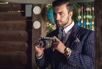 Portrait of young beautiful fashionable man in blue classic suit with retro photo camera.