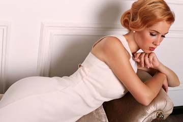 beautiful young woman with short red hair in retro style,wears elegant white dress