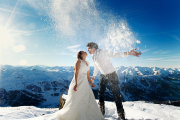 bride and groom in love throw snow on the background of the Alps