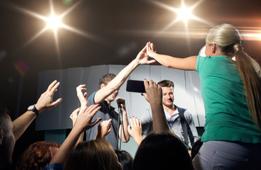 fan making high five with singer at club concert