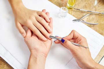 Cuticle pusher tool in nails salon woman hands