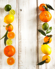 Fresh citrus fruits with leaves on wooden background