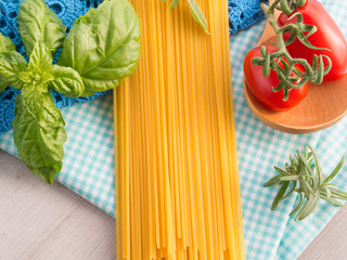 Still life with raw dry traditional spaghetti with herbs and tomatoes on checkered table cloth and gray wooden background