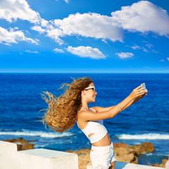 Blond teen girl photo selfie on smartphone at beach