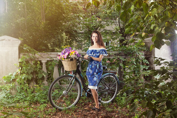 Girl with a vintage bicycle and a basket of flowers