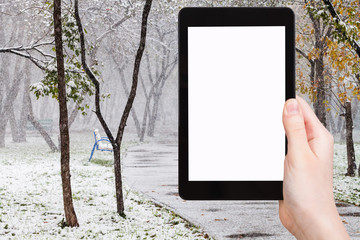 tablet pc and first snowfall in public garden