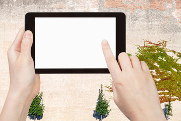 hands with tablet with cutout screen and wall