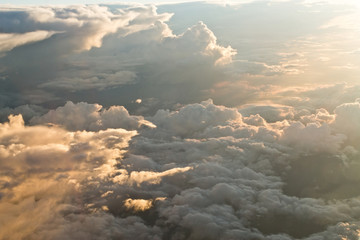 view from the airplane at the clouds, illuminated by the setting sun