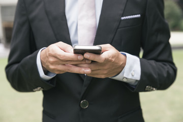 handsome business man writting email or message on phone