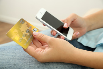 Female's hands hold credit card and cellphone, close up