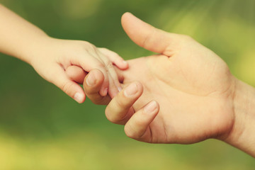 Father's hand lead his child daughter outdoors on green defocused background, trust family concept
