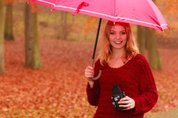 Woman with old vintage camera and umbrella.