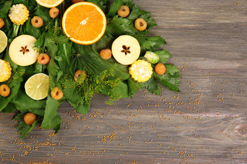 Beautiful designed bouquet of fruits and vegetables on wooden background, close up