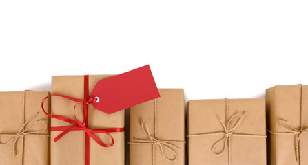 Border of brown paper parcels, one unique with red ribbon bow and gift tag