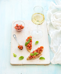 Tomato and basil bruschetta sandwich on white wooden serving board over rustic blue background, top view