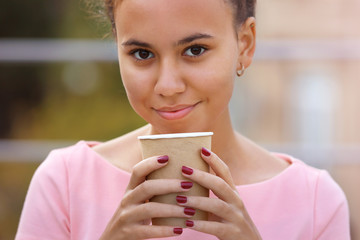 Close up portrait of pretty young woman in pink dress drinking coffee