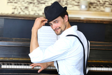 Handsome young man in hat poses with piano